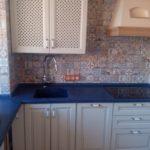 Маленькая бежева кухня с синей столешницей