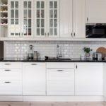 Небольшая белая кухня со стеклянными шкафчиками