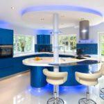 Огромная кухня с синей мебелью и шикарным островом с барной стойкой