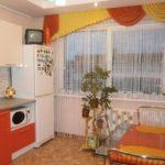 Желто-оранжевый ламбрекен на кухонном окне