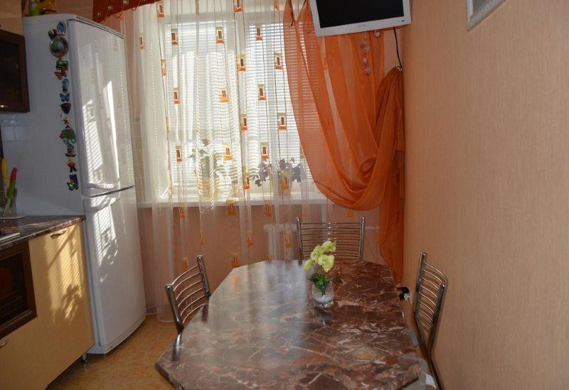 Легкая оранжевая штора на кухонном окне