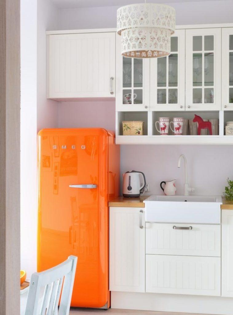 Оранжевый холодильник в кухне с белой мебелью