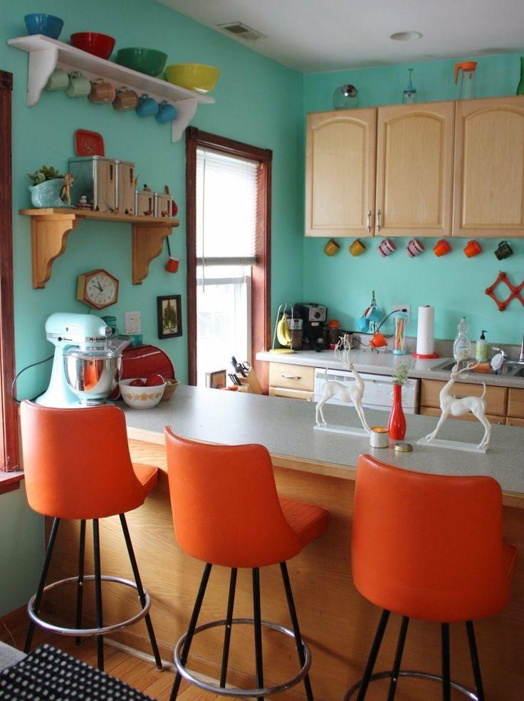 Мятные стены в кухне с оранжевыми стульями