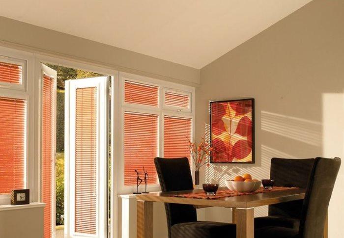 Столовая зона просторной кухни с персиковыми жалюзи