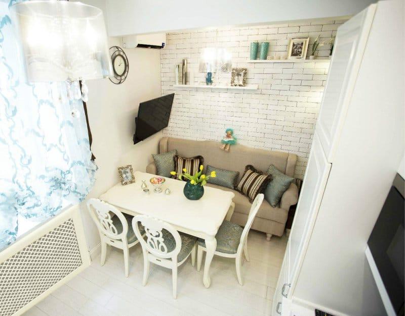Уютная кухня с прямым диванчиком в обеденной зоне