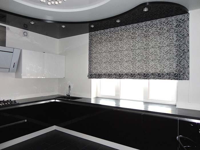 Серая римская штора на окне кухни с черной мебелью