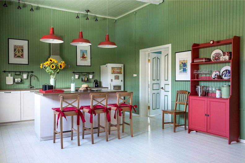 Розовый кухонный шкаф на фоне зеленых стен