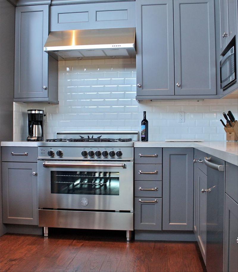 Серая плита с подвесной вытяжкой в угловой кухне