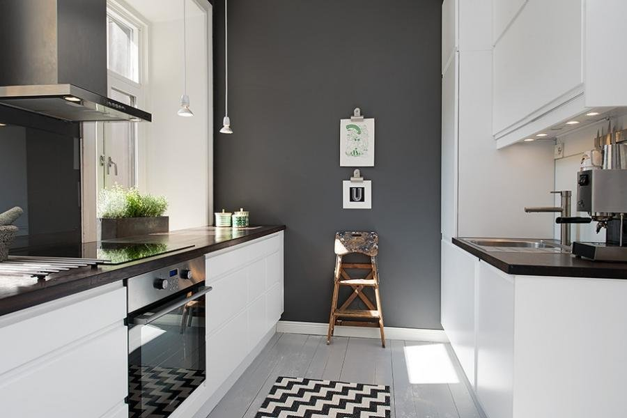 Белая мебель в узкой кухне с серой стеной