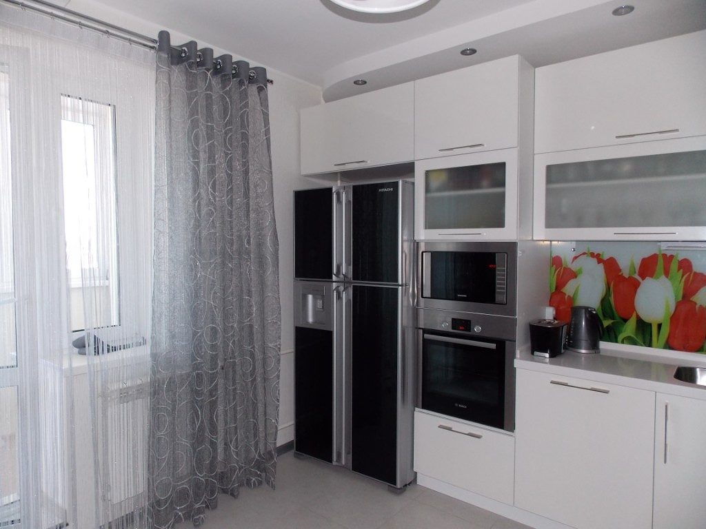 Серая вуаль на кухонном окне в городской квартире