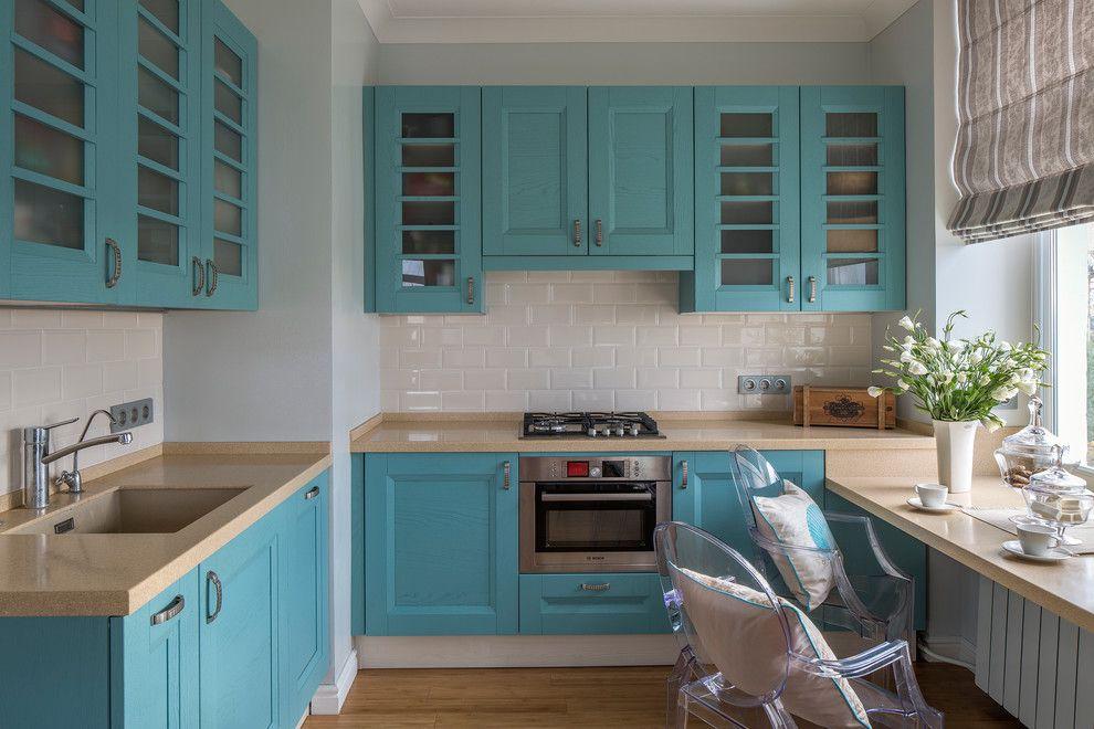 Угловая кухня с голубым гарнитуром и столом вместо подоконника