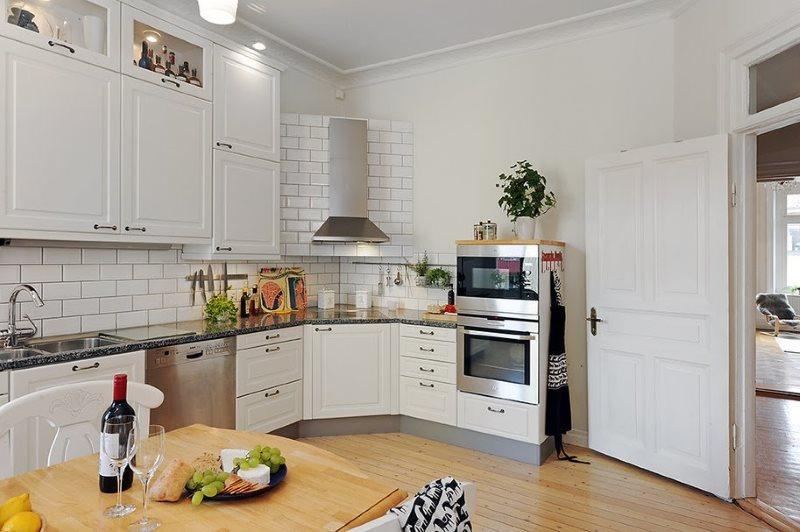 Интерьер светлой кухни с плитой в углу комнаты