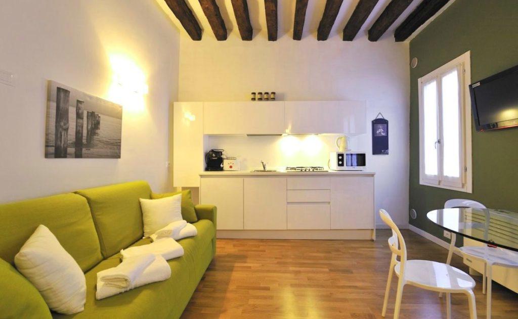 Узкий прямой диван зеленого цвета в просторной кухне