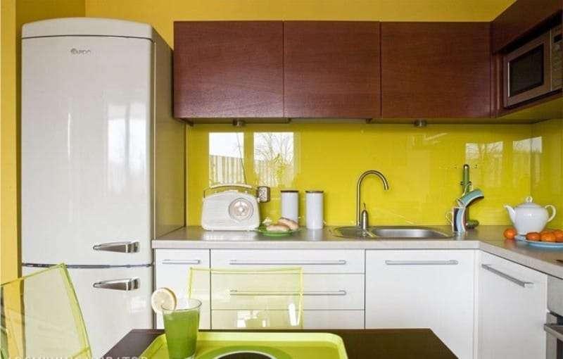 Коричневые подвесные шкафы на фоне желтой стены кухни