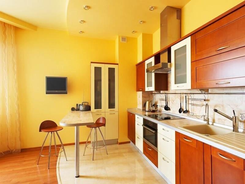 Линейная кухня с двухуровневым потолком желтого тона