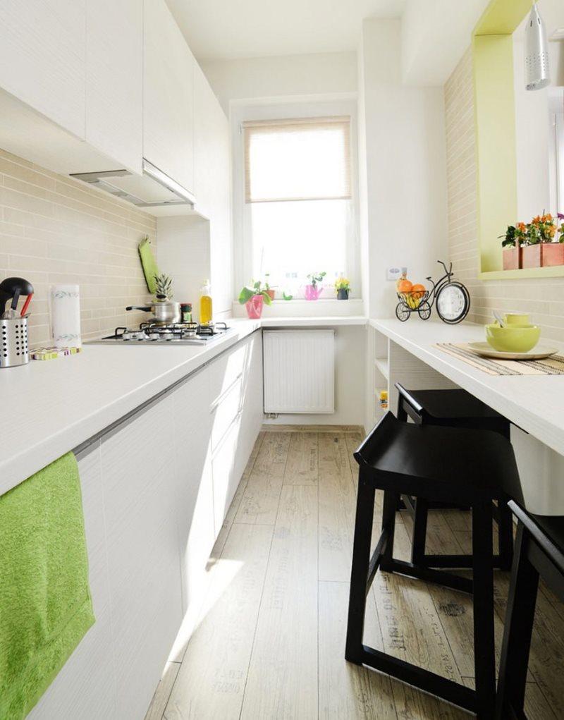 Белый гарнитур в узкой кухне с окном в конце комнаты