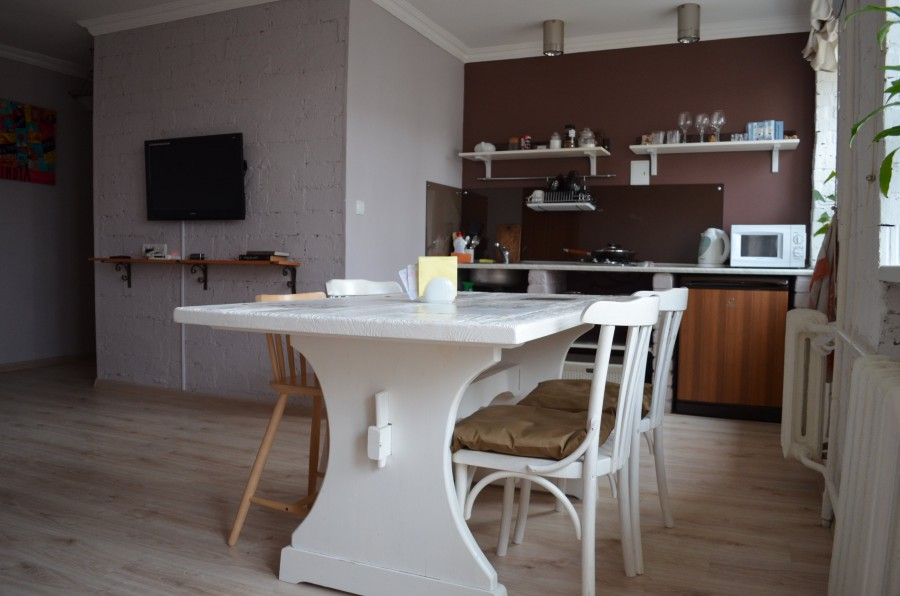 Белый стол в обеденной зоне кухни-гостиной