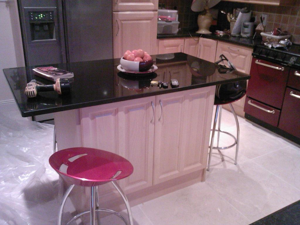 Черная столешница кухонного острова с розовыми дверками