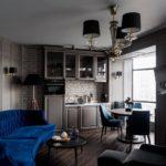 Темно-синий диван в кухне-гостиной
