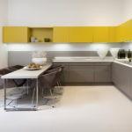 Угловая кухня с желтыми навесными шкафами