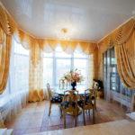 Золотистые шторы на окнах кухни-гостиной
