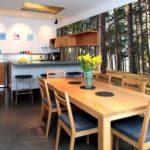 Деревянный стол в кухне с модными обоями