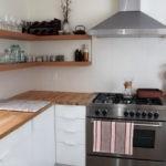 Открытые полки в углу кухни с белыми стенами