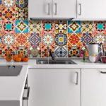 Яркий мозаичный фартук между светло-серыми фасадами гарнитура