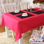 Черные салфетки под посуду на красной скатерти