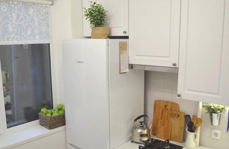 Белый холодильник около окна в хрущевке