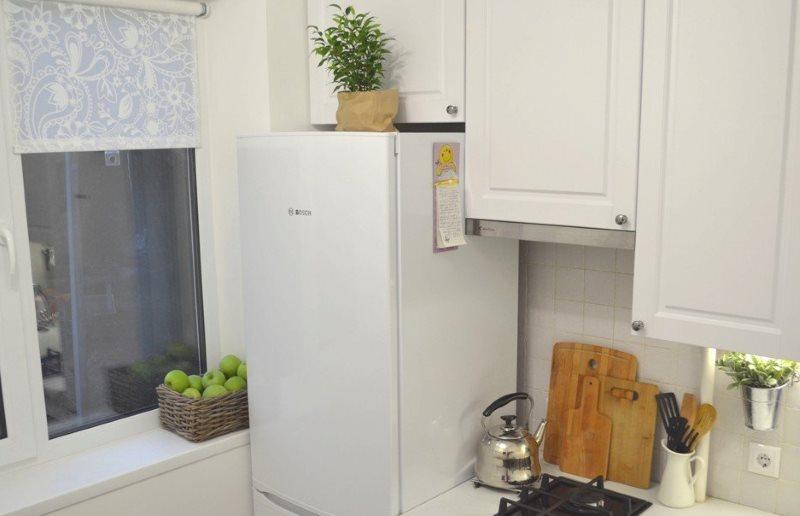 Белый холодильник возле кухонного окна