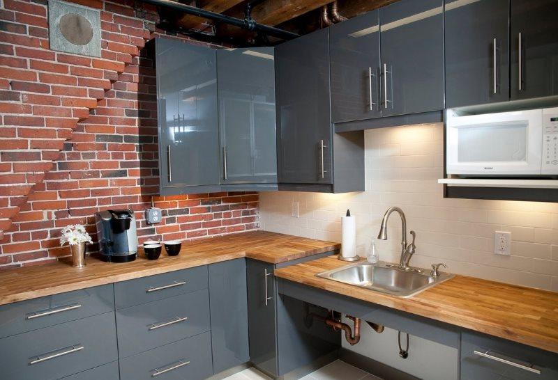 Бежевый фартук на кухне с кирпичной стеной