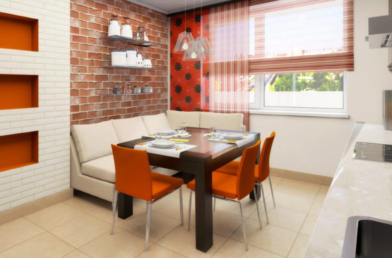 Оранжевые стулья в обеденной зоне кухни с диваном