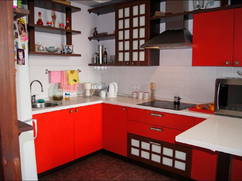 Деревянные полки на стене кухни с красными шкафами