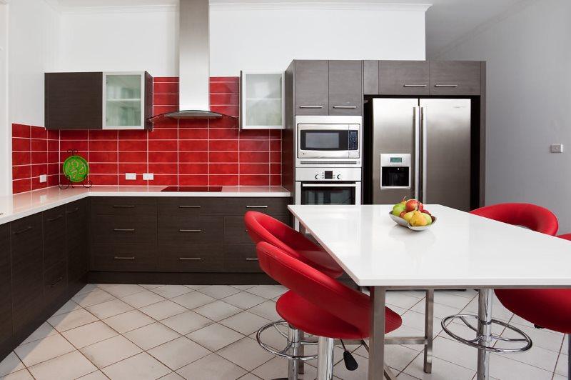 Красные стулья со спинками за белым кухонным столом
