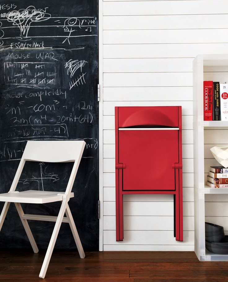 Красный складной стул в сложенном состоянии на стене