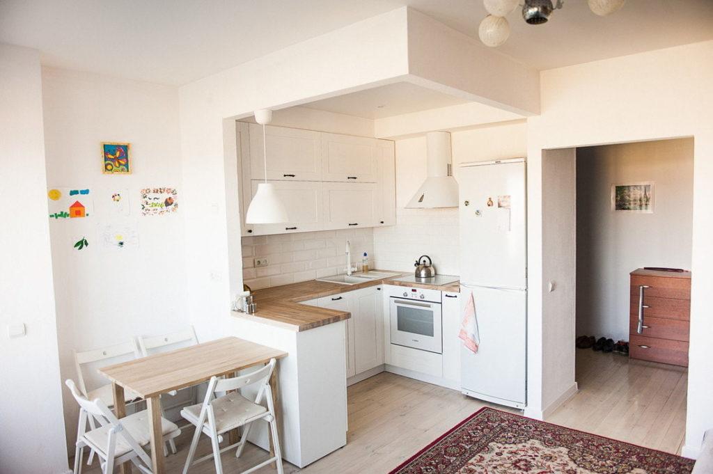 Интерьер белой кухни-гостиной в квартире студии