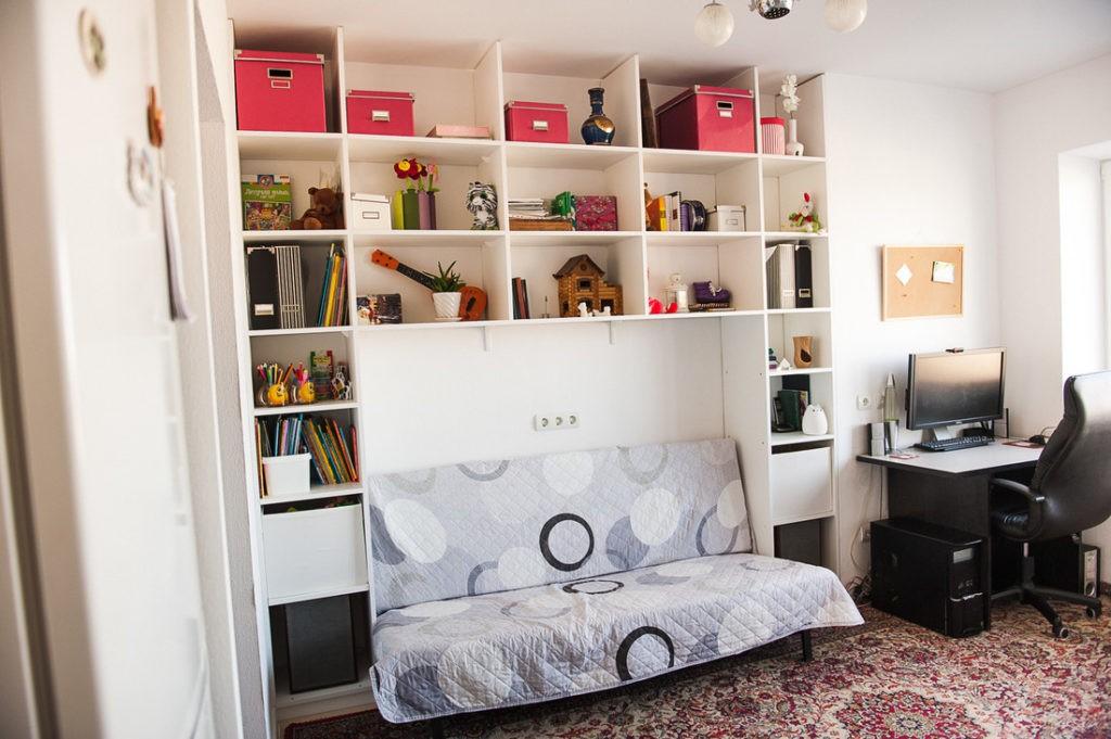Открытые полки над диваном в белой кухне-гостиной