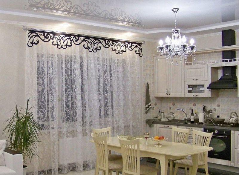 Черный ламбрекен ажурного типа на окне с белым тюлем