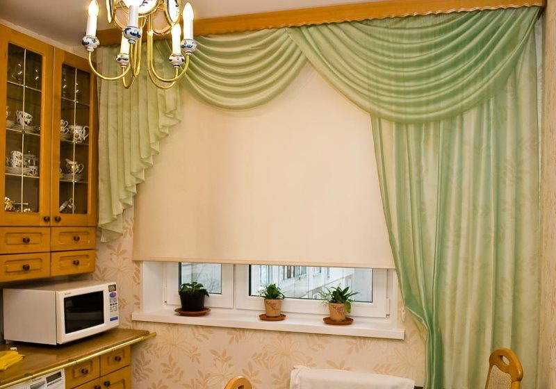 Бежевая рулонная штора на окне кухни с зеленым ламбрекеном