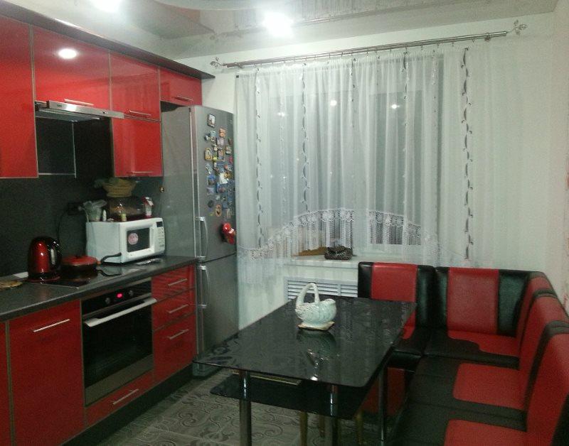 Полупрозрачная занавеска на окне кухни с красной мебелью