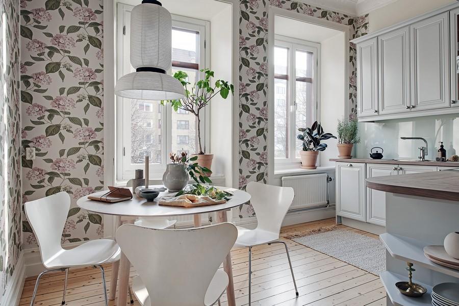 Зеленые листики на обоях в кухне с белой мебелью