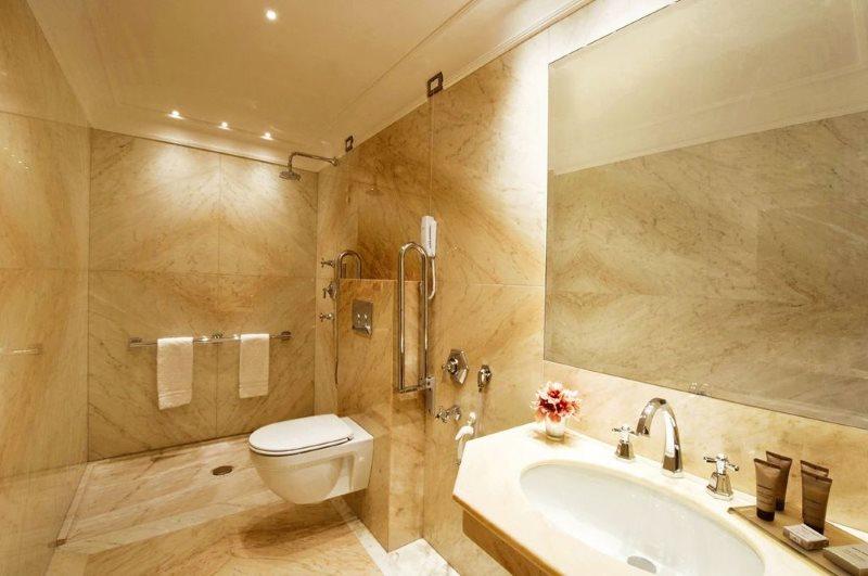 Мраморная плитка на стене совмещенной ванной комнаты