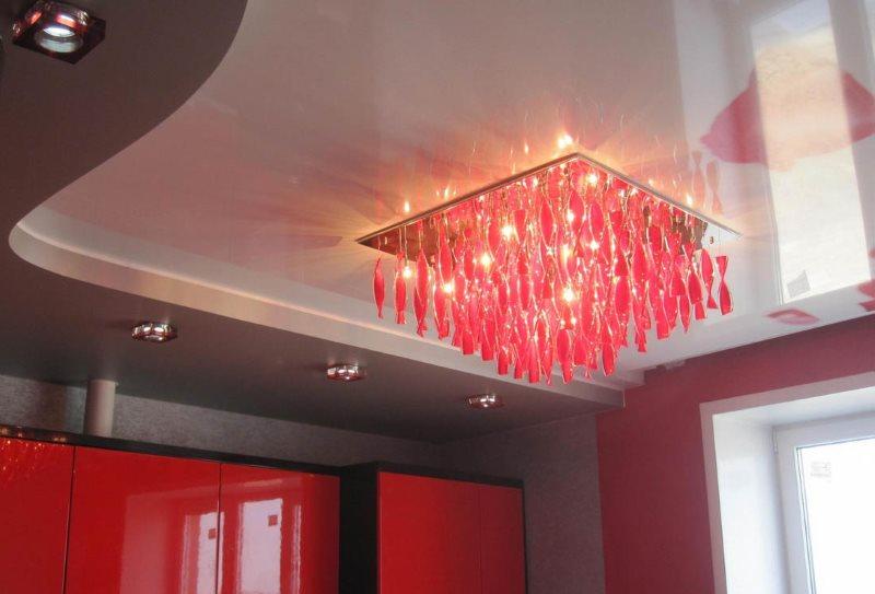 Красный светильник на натяжном потолке кухни