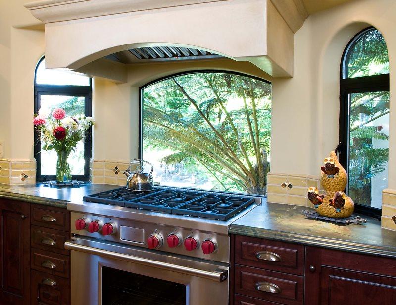 Газовая плита с вытяжкой перед кухонным окном