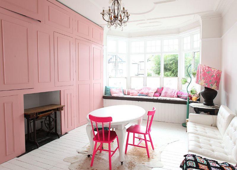 Розовые стулья вокруг белого стола овальной формы