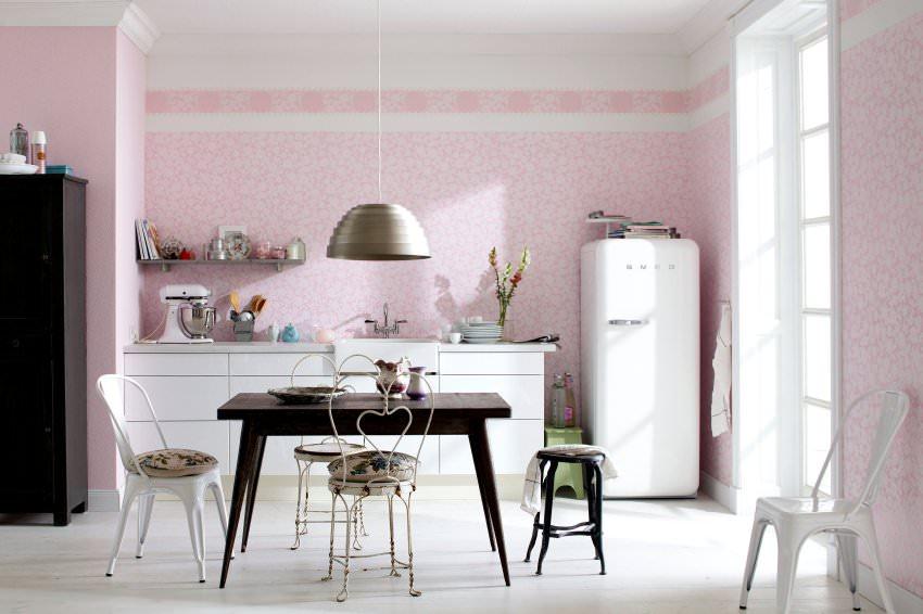 Белый холодильник на фоне розовой стены