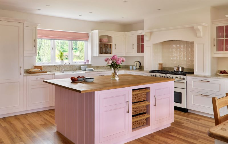 Деревянная столешница кухонного острова с розовыми фасадами