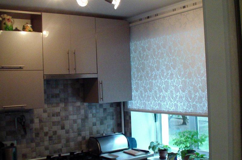 Светлая рулонная штора на окне маленькой кухни