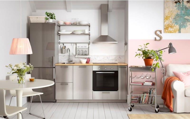 Серый гарнитур в кухне с розовой стеной